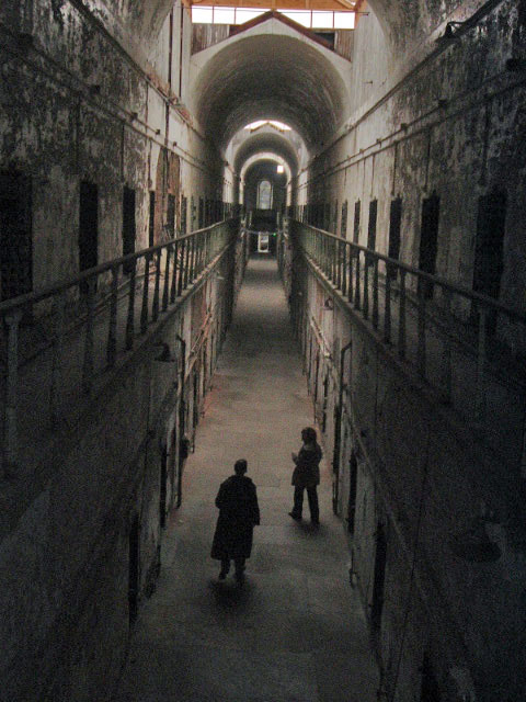 Two men walking through the hallway of an old prison.