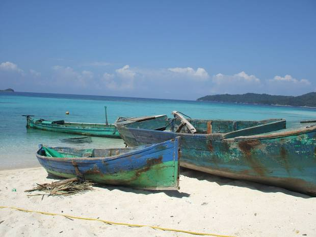 Three old fishing boats on the shore of a beach.