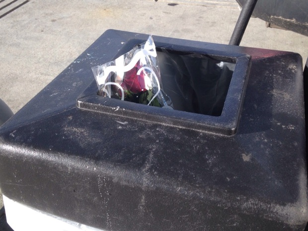 A bouquet of roses in a black trash can.