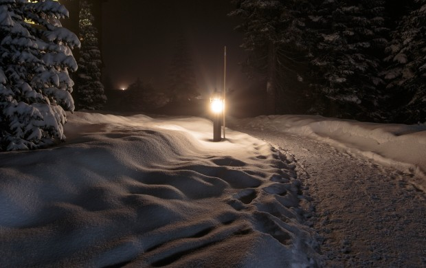 A lit post next to a path, the ground covered in snow.